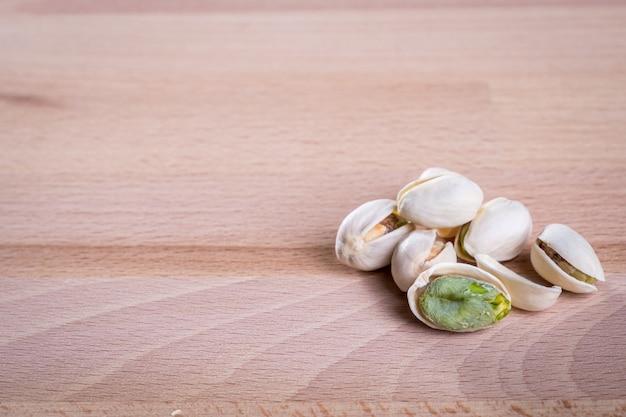 木製の床の背景にシェルとピスタチオナッツを閉じます。