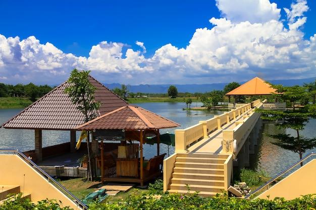 三角形の屋根には緑色の山々がある水の真ん中に長い廊下があります。