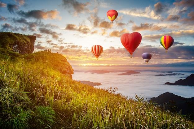 カラフルな熱気球がタイ北部、チェンライ県、プチェファの山の上を飛んでいます。