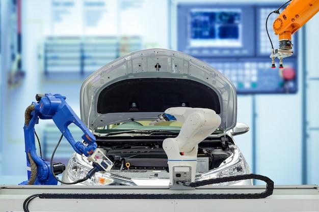 Промышленная роботизированная коллективная работа с автомобилем на размытом умном заводском фоне синего тона, работа робота вместо человека