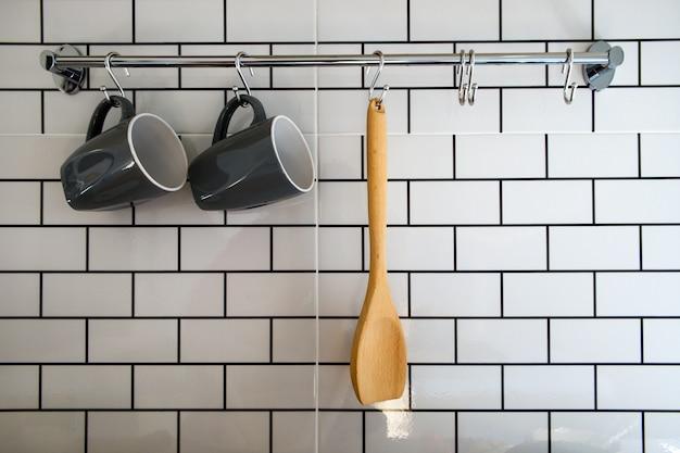 木のスプーンと白いレンガの壁にスチールレールに掛かっている灰色のコーヒーカップとクローズアップキッチンルーム