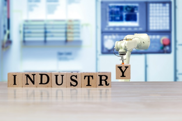 Промышленный робот выбирает деревянное письмо для сообщения о сборке на деревянном столе и цвет машины синего тона