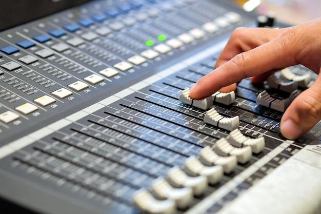 サウンドエンジニアの指がレコーディングルームのボタンのオーディオコントローラーを押しています。