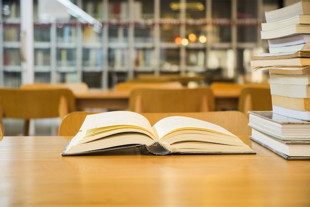 古い教科書が開いており、図書室のぼやけた本棚の木製テーブルに置かれた本をスタック