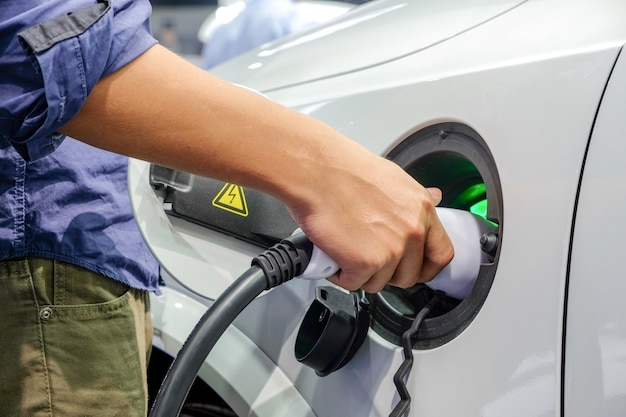 新しい車の電化に燃料を供給しているクローズアップの男性の手