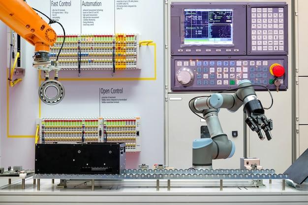スマートな工場でコンベヤベルトを介して作業する産業用ロボット
