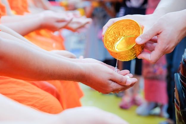ソンクラーン祭りの修道士の手に水(水浴)を注いでいるクローズアップタイ人