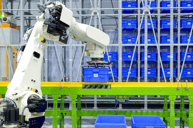 産業用ロボット把持青いプラスチック製の箱の容器は、スマートな工場倉庫のコンベヤーに置かれます