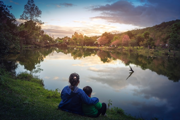 姉妹と兄弟が一緒に湖の日没を見ている。