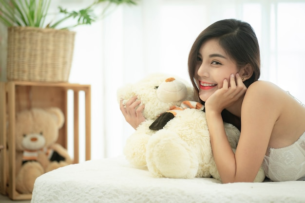 若い美しいアジア女性がベッドの上の白いセクシーなランジェリーでポーズします。