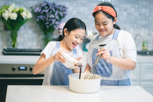 Две маленькие сестры готовят торт тесто.