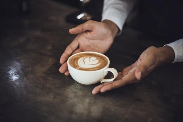 男性バリスタは、コーヒーショップで顧客のためにコーヒーを準備します。コーヒーショップでクライアントにサービスを提供するカフェのオーナー。