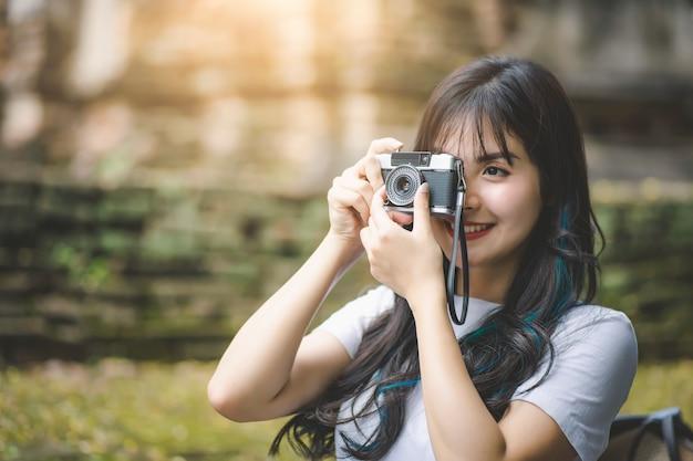 Молодая азиатская женщина путешественника усмехаясь пока путешествующ вокруг тайского древнего храма на каникулах праздников.
