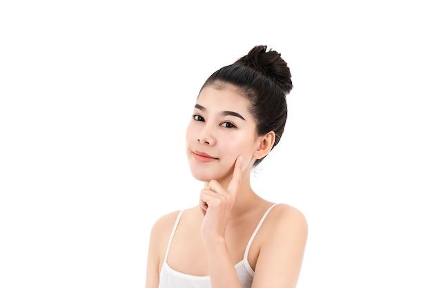 美肌と顔が白い表面に分離された魅力的なアジアの若い女性の肖像画。健康な肌と顔のケアの概念。