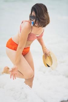夏休みビーチで幸福の感情で遊んでビキニスーツを着ている若い女性