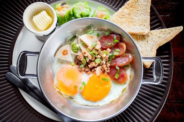 食べる準備ができて金属皿に豚肉とパンで揚げた朝の卵