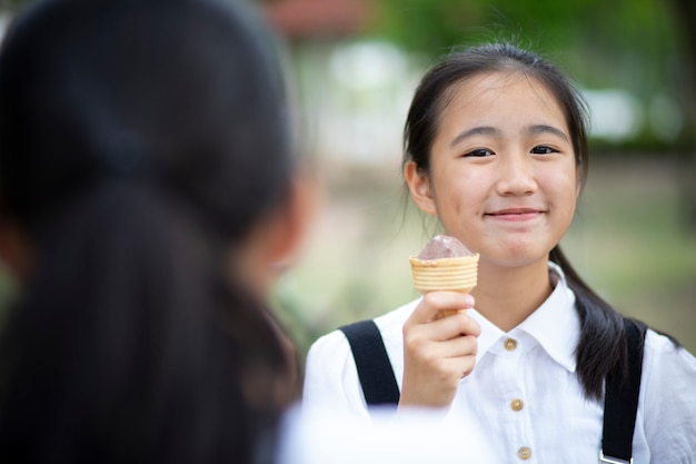 幸福の顔とアイスクリームを食べるアジアのティーンエイジャー