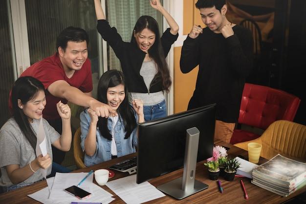 アジアの若いフリーランスのチームワークの仕事成功幸福感情