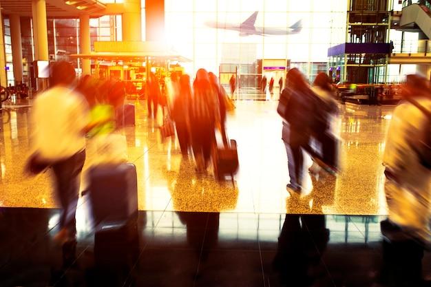 Люди с дорожным багажом гуляют в терминале аэропорта