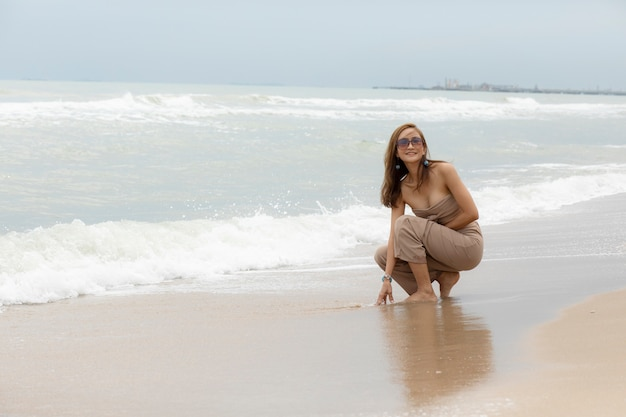 海のビーチで幸せな感情とリラックスできる美しい女性