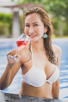 ビキニの女性とスイミングプールで赤い飲料のガラス
