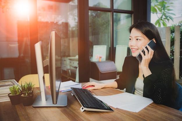 アジアの若い女性が携帯電話に取り組んで、オフィスでコンピューティング