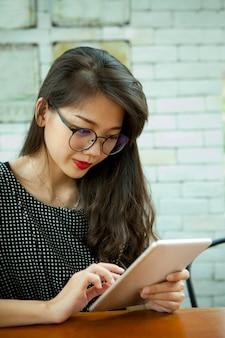 Азиатское сообщение чтения молодой женщины на таблетке компьютера