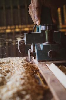 自宅のワークショップで働く木材ドリルマシンを閉じる
