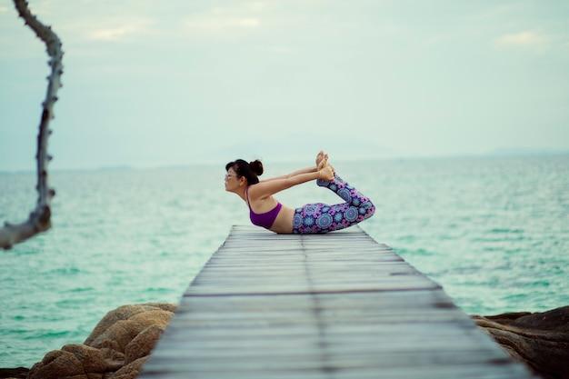 海の木製の桟橋でカメのポーズでヨガをしている美しい女性