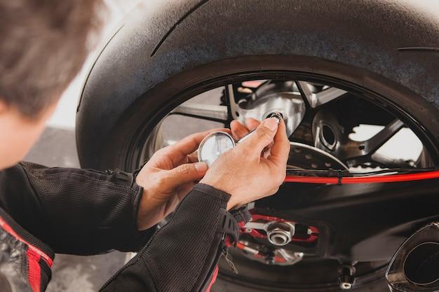 安全乗用車の旅行前に男のオートバイタイヤ手動空気圧テスト