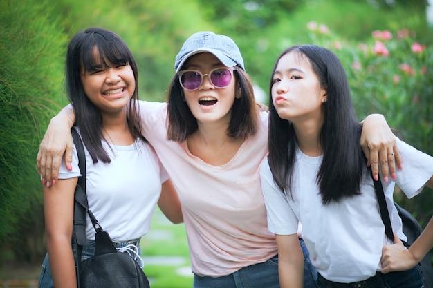 Азиатская женщина и два подростка довольны отдыхом в зеленом парке
