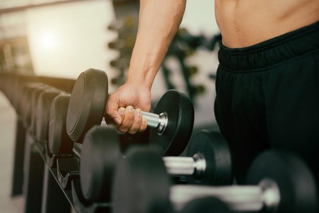 Сильный человек фитнес создает мускулистое тело и делает упражнения