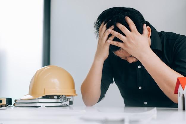 ビジネスの男性は、医療概念のオフィスで働いている間彼らの心に頭を感じる