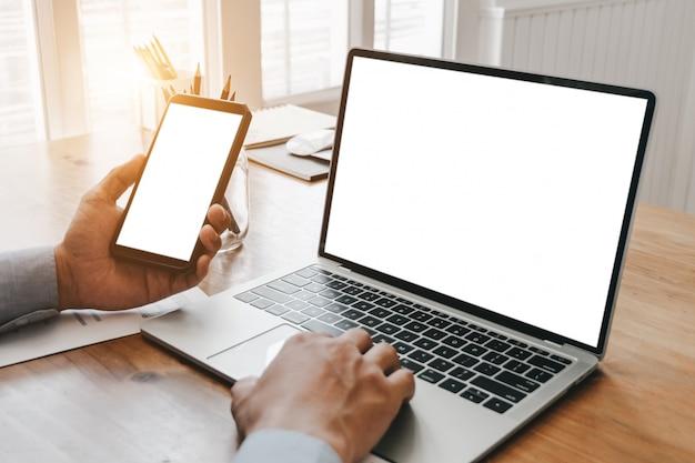スマートフォンノートパソコンとオフィスでドキュメントを扱うビジネスの女性を閉じる
