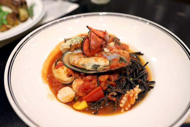 Черные спагетти обжаривают с морепродуктами, такими как лобстер, мидии, кальмары, морские гребешки в белом блюде в ресторане блэк из чернил кальмара.