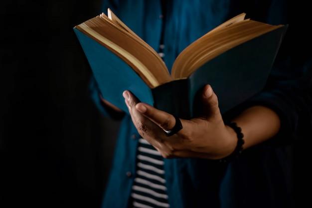 読書のコンセプト。開いた聖書の本を手に持っている人。ダークトーン、