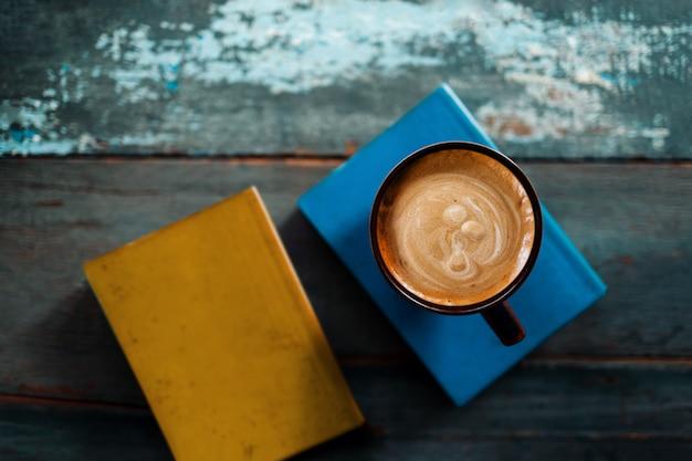 リラクゼーション。居心地の良い場所やカフェ、トップビュー、セレクティブフォーカスで本とコーヒーを読んでリラックス