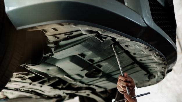 メカニックが仕事をしています。車の修理ステーションのリフトアップマシン上の車。修理サービスとメンテナンス。セレクティブフォーカス