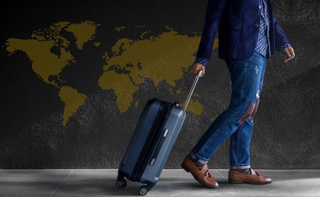 Путешествовать . молодой человек с багажом, проходя мимо стены. карта мира