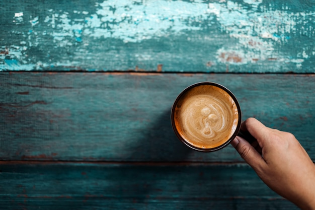 古い青いテーブルでコーヒーを飲む人
