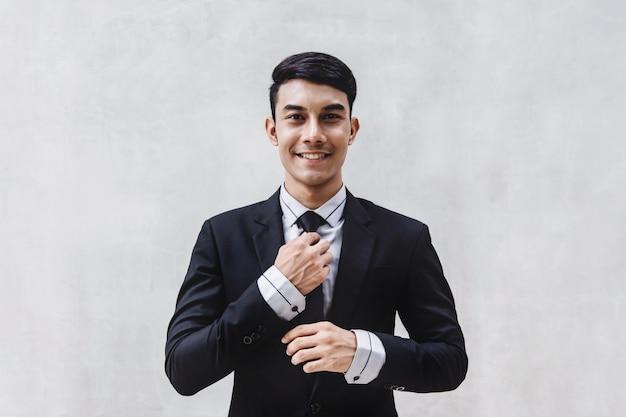 黒のフォーマルスーツで幸せなビジネスマンの肖像画。セメント壁のそばに立つ