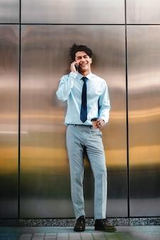 都市で携帯電話を使用して幸せな青年実業家。現代人のライフスタイル。正面図。コーヒーカップと壁のそばに立っています。