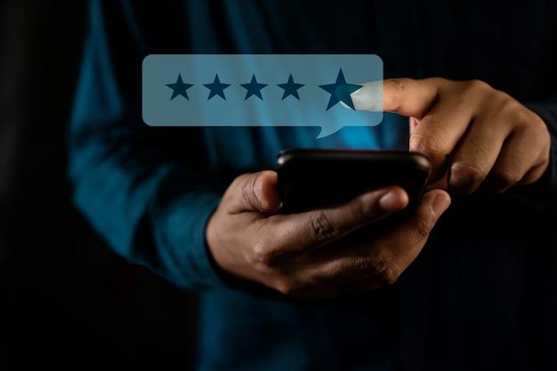 顧客体験のコンセプト。スマートフォンで肯定的なレビューのための星評価を与える現代人