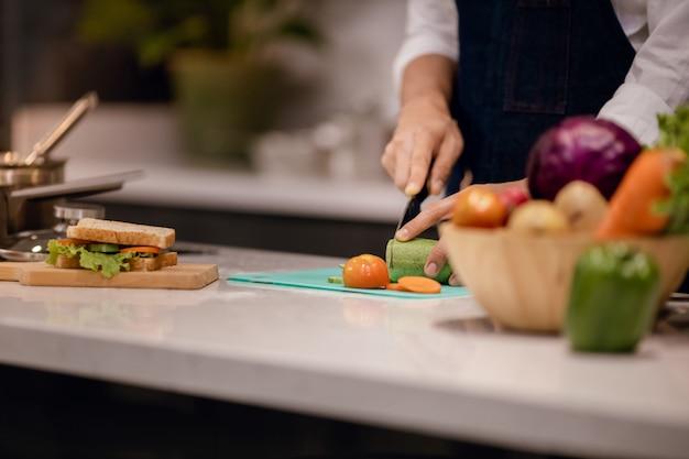 自宅のキッチンで朝食のサンドイッチを作るシェフ。テーブルの上の野菜をスライスする手。