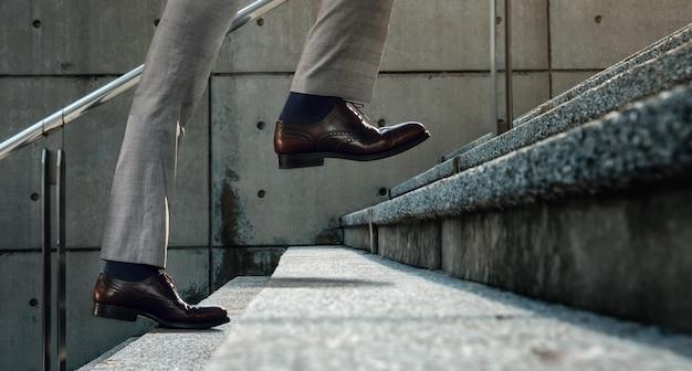 Мотивация и сложная концепция. шаги вперед к успеху. низкая часть бизнесмена, идущего по лестнице