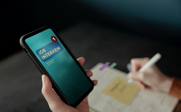 Напоминание о собеседовании на экране мобильного телефона. безработная женщина с помощью смартфона, чтобы назначить встречу для новой карьеры. концепция занятости и найма