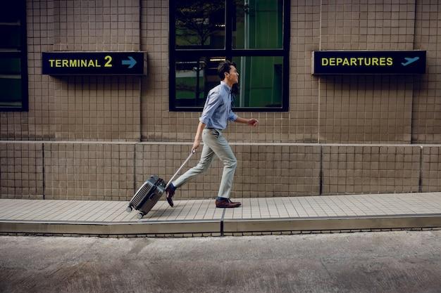 Спешите в интернат. улыбающийся пассажир бизнесмен работает и потянув багаж в аэропорту. отправление и терминал вход в качестве фона