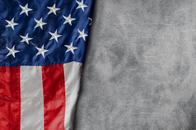 ブランクセメントの背景に自由に横たわるアメリカの旗