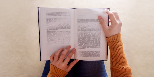居心地の良い家の本でリラックスした若い女性のソフトフォーカス