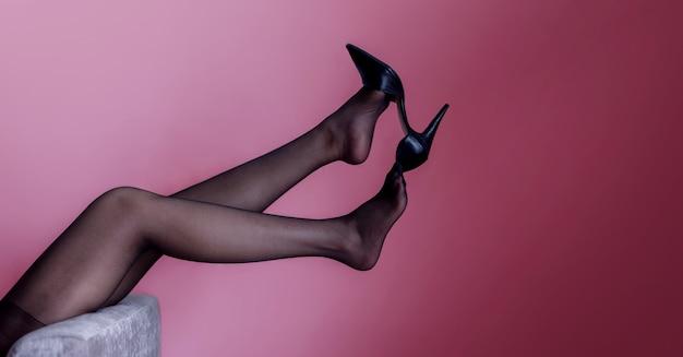 Сексуальные ноги женщины пытаются снять обувь на высоком каблуке